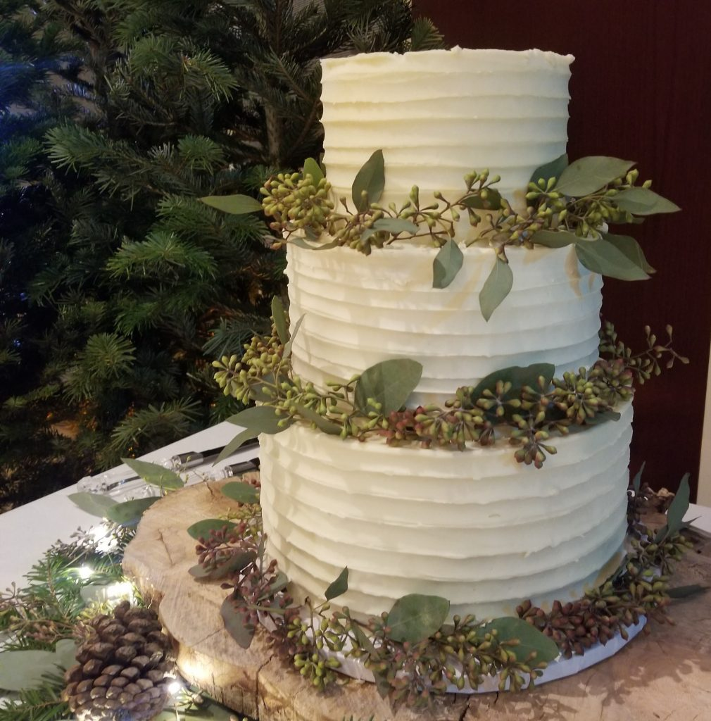 Wedding Cake decorated with Perfectly Perfect Vanilla Buttercream, surrounded with greenery.