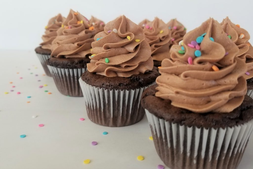 Easy Nutella Frosting piled high onto chocolate cupcakes with rainbow sprinkles